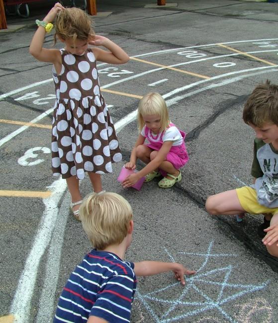 Dzieci rysują kredą na betonie