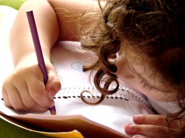 Dziewczynka pisze w zeszycie