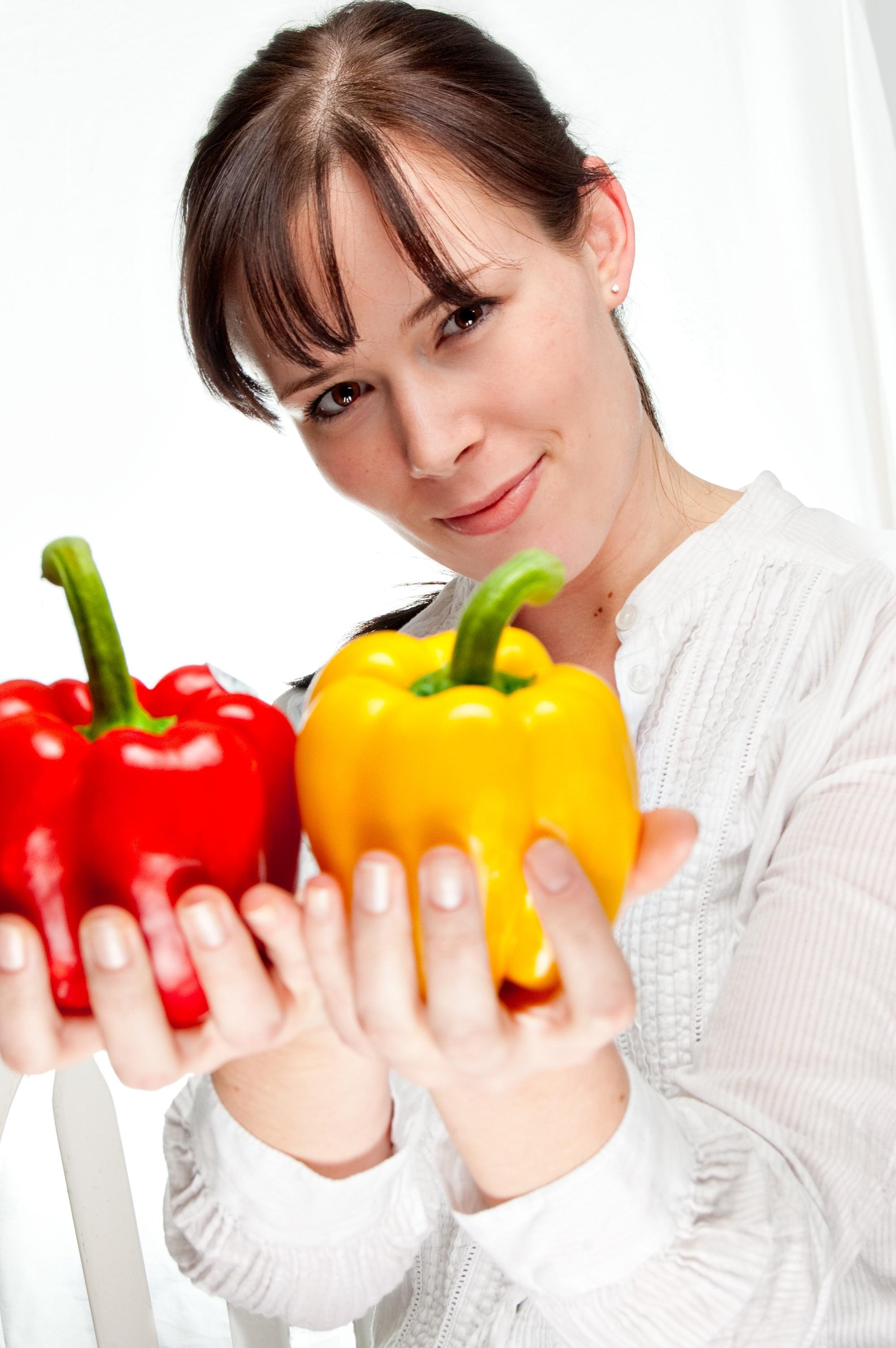 Raw food - kobieta trzyma paprykę w dłoniach